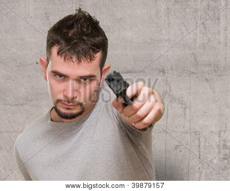 portrait of serious man pointing with a gun against a grunge background
