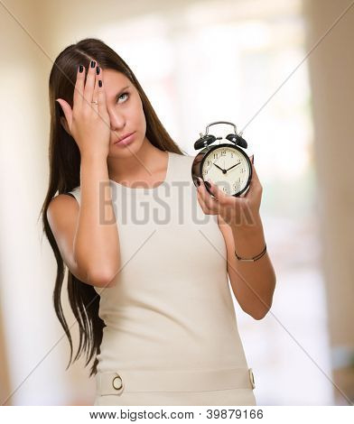 Tired Woman Holding Alarm Clock against an abstract background
