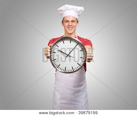 portrait of young cook man holding clock over grey background