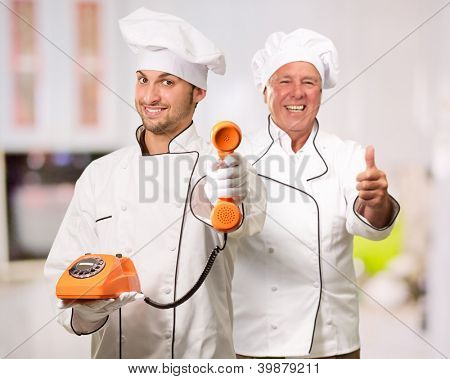 Young Chef Holding Telephone In Front Of Mature Chef, Indoor