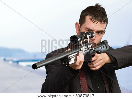 Young Man Aiming With Rifle at a port