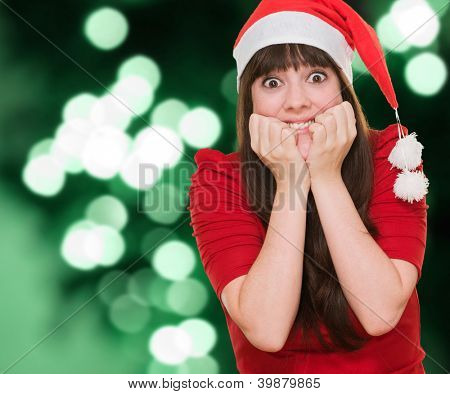 Extremely excited woman wearing a christmas hat against a background of green shiny lights