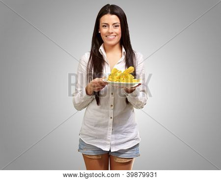 portrait of young woman holding a potato chips plate over grey background