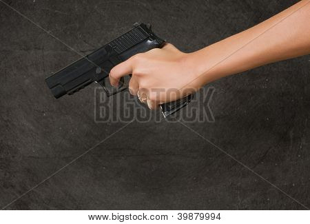 Woman's Hand With A Gun against a grunge background