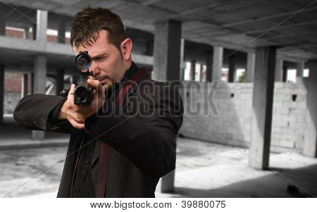 Man aiming with rifle, indoor