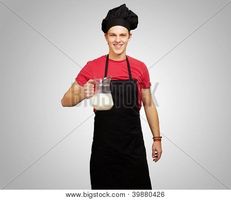 portrait of young cook man holding milk jar over grey background