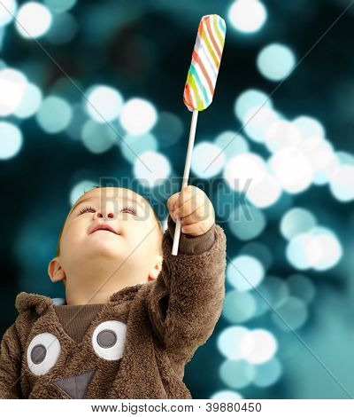 Portrait Of Baby Boy Holding Lollipop against a background of shiny blue lights