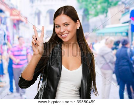 Pretty Young Woman Giving Victory Sign at a market, outdoor