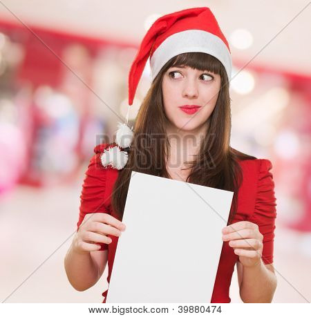 worried christmas woman holding a blank card, indoor