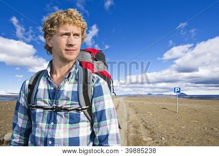 Portrait of a hiker in front of the vast, volcanic tundra landscape of Sprengisandur in Iceland, in the middle of nowhere, in between two major glaciers on the volcanic Mid Atlantic Ridge