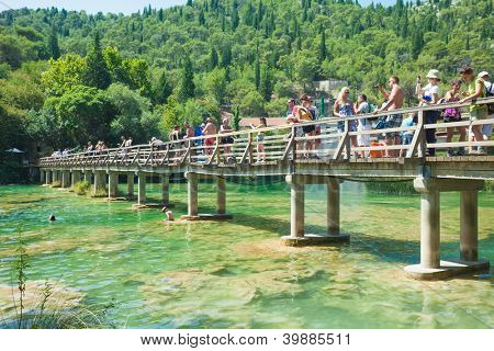 KRKA, CROATIA - JULY 28, 2012: People on the bridge over Krka on July 28, 2012 in Krka, Croatia. The Krka National Park is one of eight national parks in Croatia.