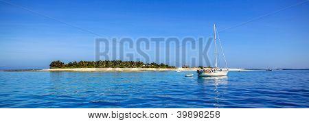Boat and beautiful Fiji atoll island with white beach