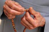 stock photo of prayer beads  - hand of a catholic nun counting the rosary - JPG