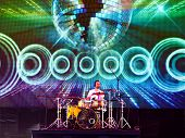 Drummer plays in front of large LED screen