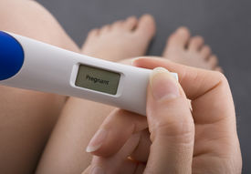 pic of pregnancy test  - Woman taking a pregnancy test showing pregnant result - JPG