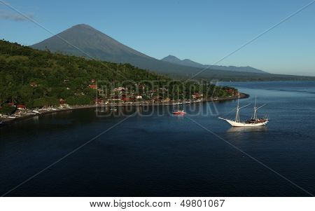 Calm lagoon with village on the coast and volcano (Agung) on the background. Bali, Indonesia