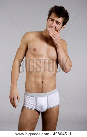 Portrait of young adult sleepy man naked muscular torso in white panties isolated on grey background