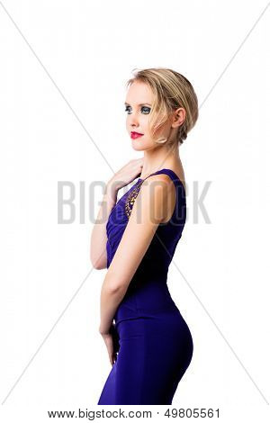 young beautiful woman with up style blond hair wearing tight blue evening dress with gold luxury design on her fit slim body over white studio background