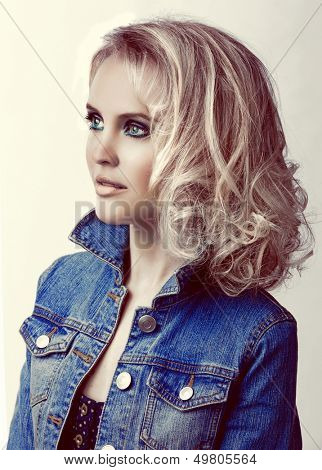 portrait of a young beautiful woman with loose curly hair blond hair wearing blue jean jacket with retro effect