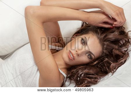 Portrait Of Cute Brunette Woman Relaxing On Bed.
