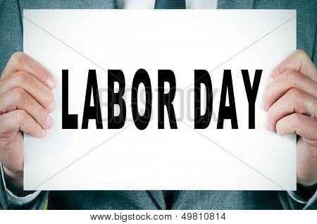 a man wearing a suit holding a signboard with the text labor day written on it