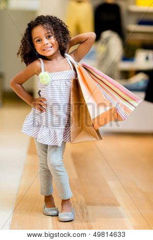 Beautiful shopping girl at a retail store holding bags