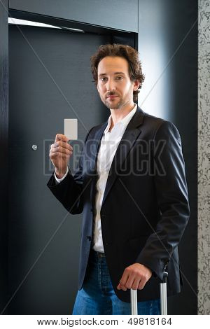 Young business man standing with a keycard in front of a room door in a hotel