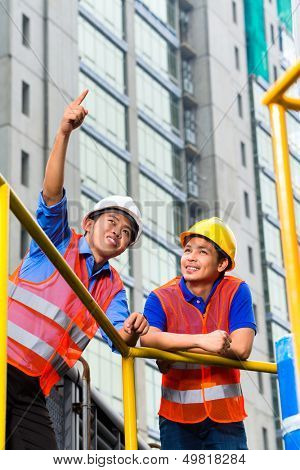Chinese architect and supervisor point on building site into the distance