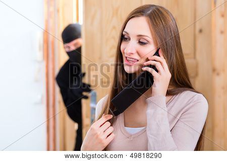 Security - disguised burglar breaking in an apartment or office and standing behind the innocence victim