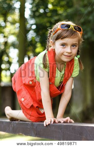 Happy Young Girl Crawl On The Beam In The Park