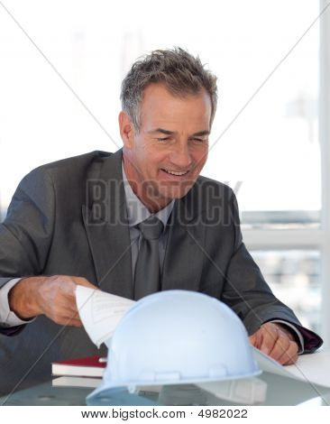 Mature Business Man Looking At Blueprints