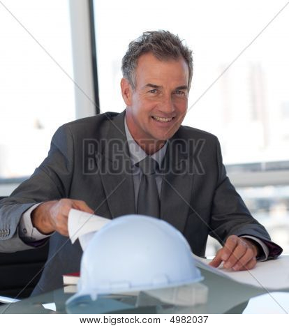 Mature Business Man Looking At Blueprints