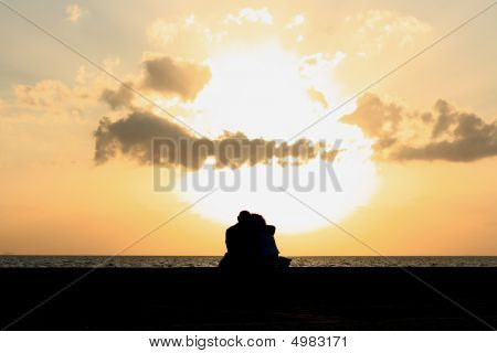 A Couple Sitting Together At The Sunset