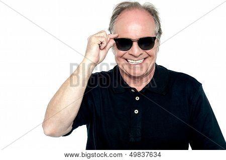 Fashionable Cheerful Aged Man Adjusting His Shades