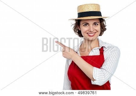 Cute Woman In Hat Pointing Sideways