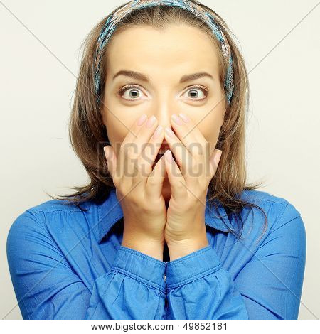 Young woman with hands over mouth. Surprise!