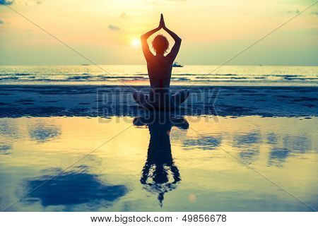 Yoga woman sitting in lotus pose on the beach during sunset, with reflection in water (cross-process style)