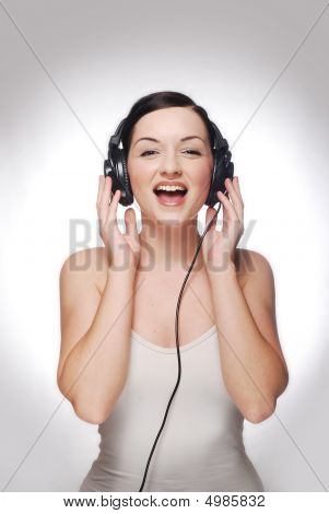 Smiling Girl Wearing Headphones On A Background With Gradient.