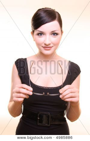 Smiling Young Woman Holding Glasses On Beige Background