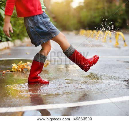 Niño llevando lluvia roja botas saltar en un charco