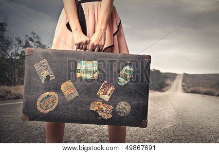 young woman with a vintage suitcase in the middle of a deserted road