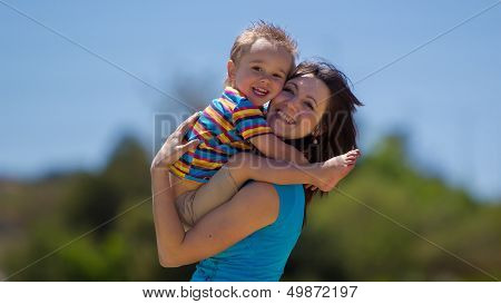 A beautiful young woman is holding her son in the air