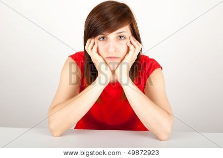 The Young Woman Is Sitting Bored At A Table