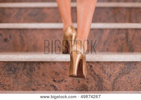 Businesswoman taking step to higher level on stairway