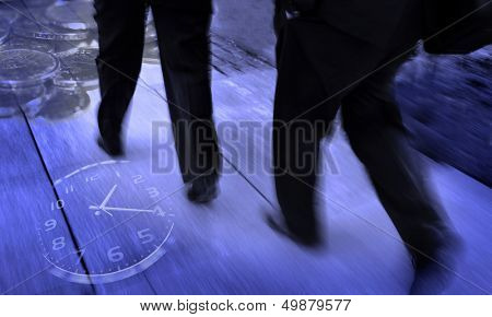 Group of businessmen walking and holding briefcases with money and a clock surrounding them symbolizing speedy business