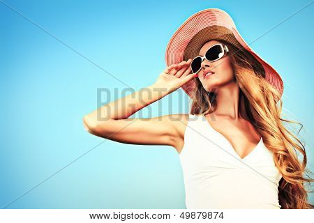 Beautiful young woman in elegant hat and sunglasses posing over sky.