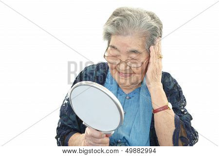 Old woman looking at herself in a hand mirror