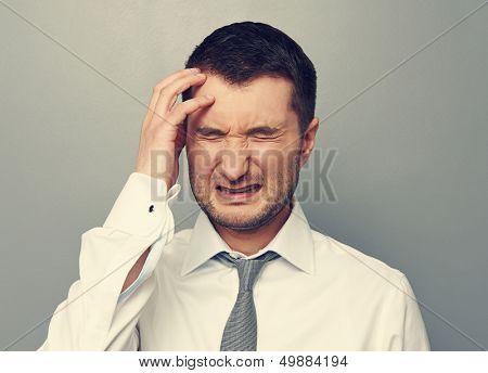 portrait of businessman with headache over grey background
