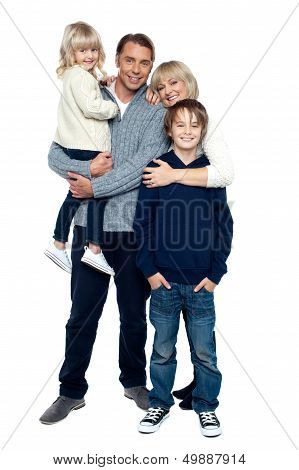 Affectionate Family Of Four Posing In Winter Outfits