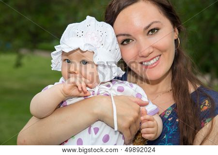 Happy Mom And Child Girl Hugging. The Concept Of Childhood And Family. Beautiful Mother And Her Baby